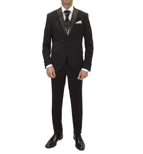 Traje negro de corte actual, pantalón y chaqueta con corbatón negro y chaleco plata.