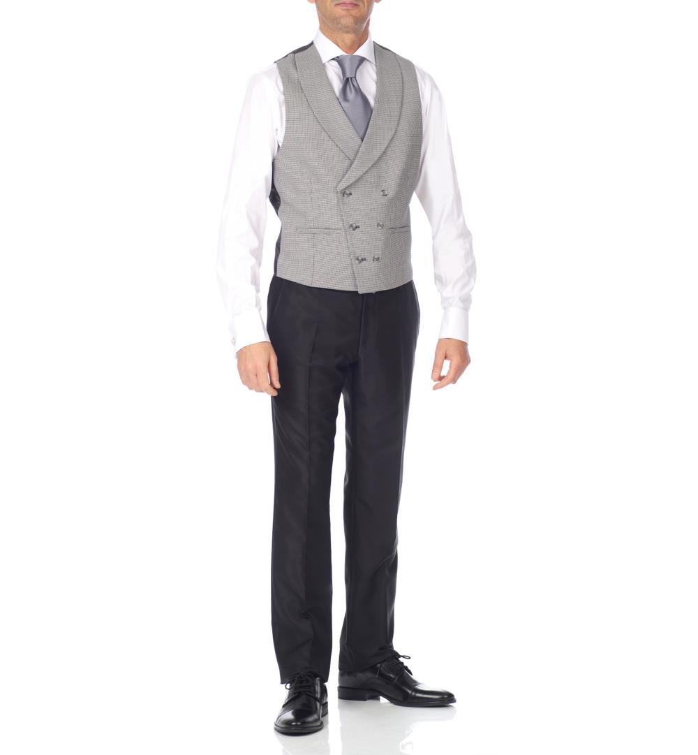 Chaleco gris y pantalón negro.